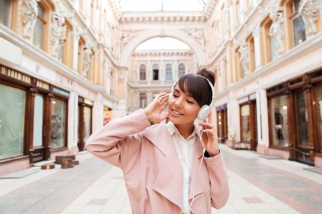 Het gelukkige jonge vrouw genieten die aan muziek op een stadsstraat luisteren