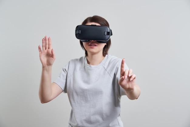 Het gelukkige jonge vrouw spelen op vr-glazen binnen, virtueel werkelijkheidsconcept met jong meisje die pret met hoofdtelefoonbeschermende brillen hebben