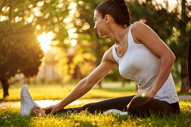 Het gelukkige jonge vrouw uitrekken zich alvorens in openlucht te lopen. mooie sport meisje in het park houdt zich bezig met fitness, warming-up.