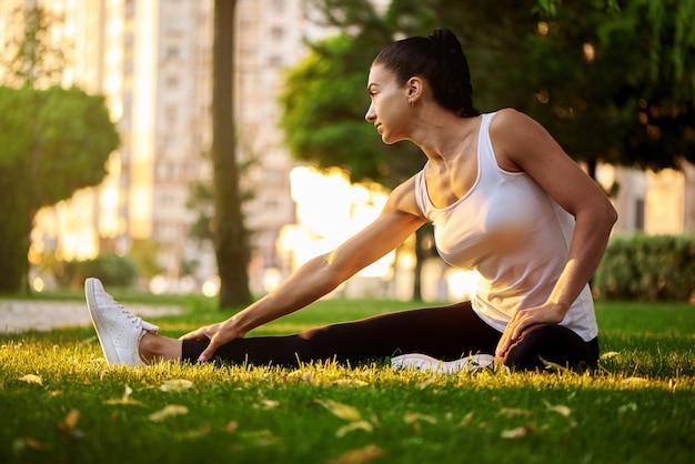 Het gelukkige jonge vrouw uitrekken zich alvorens in openlucht te lopen. mooie sport meisje in het park houdt zich bezig met fitness