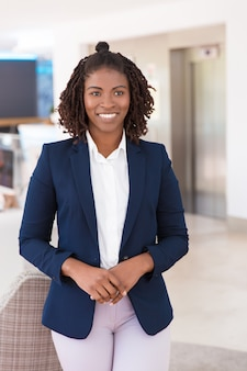 Het gelukkige jonge vrouwelijke professionele stellen in bureaugang