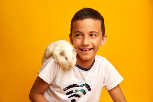 Het gelukkige jongen spelen met leuk proefkonijn