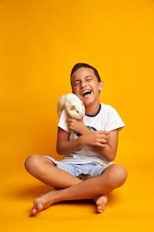 Het gelukkige jongen spelen met leuke proefkonijnen