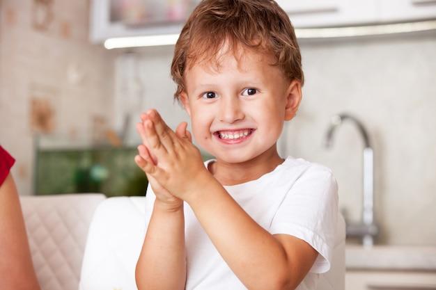 Het gelukkige jongen spelen met plasticine. vreugdevolle emoties en applaus. grappige jongen glimlacht gelukkig. overwinning emotioneel genot