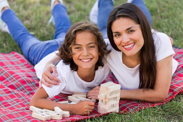 Het gelukkige jongen stellen in het park met moeder
