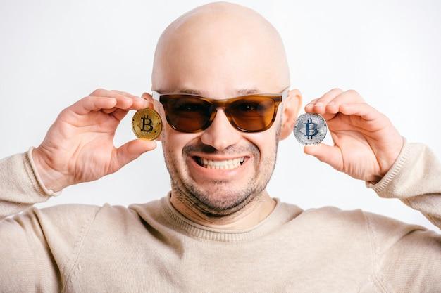 Het gelukkige kale zakenman spelen met bitcoinmuntstukken voor ogen. grappig cryptomijnwerkerportret dat op wit wordt geïsoleerd