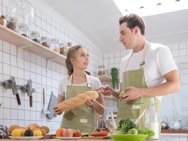 Het gelukkige kaukasische paarfamilie koken in moderne keuken thuis met liefde. gehuwde romantische man en vrouw die verse groentesalade koken gezond concept.