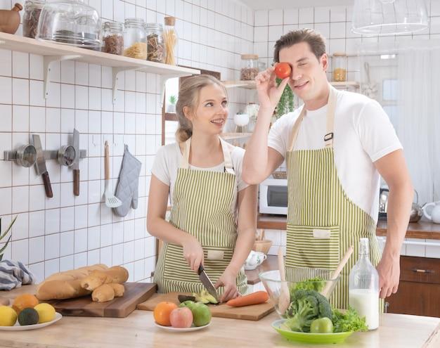 Het gelukkige kaukasische paarfamilie koken in moderne keuken thuis met liefde.