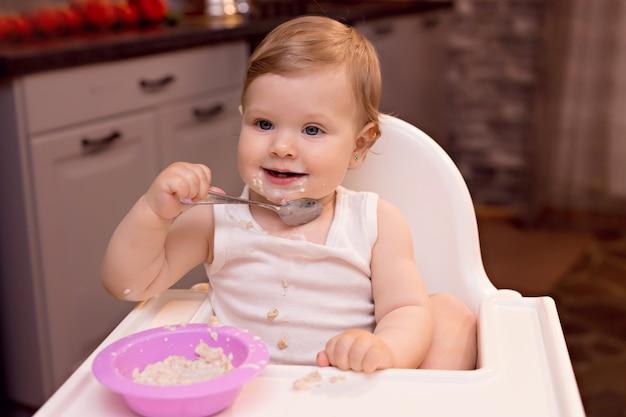 Het gelukkige kind eet melkhavermoutpap met een lepel. portret van een gelukkig meisje in een kinderstoel in de keuken