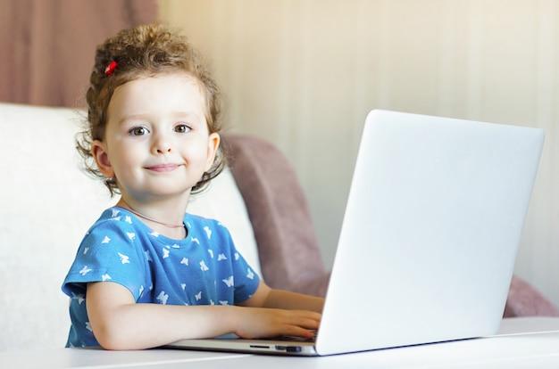 Het gelukkige kind speelt bij de computer en glimlacht. klein meisje studeert op afstand. online training. kinderen en internet. afstandsonderwijs online onderwijs. kopieer ruimte