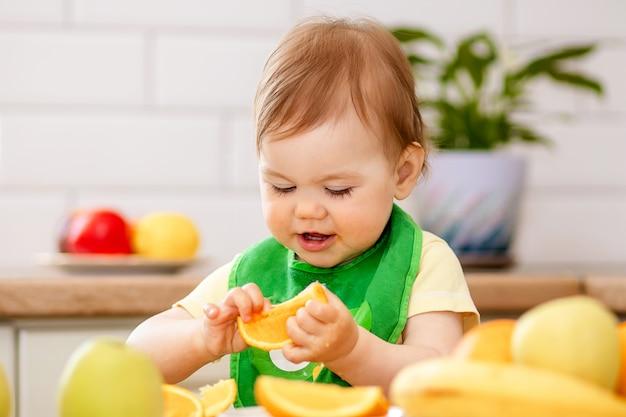 Het gelukkige kindmeisje in de keuken eet smakelijke vruchten, zoete sinaasappelen.