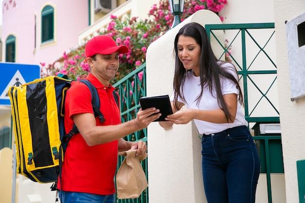 Het gelukkige klembord van de koeriersholding en het ondertekenen van de vrouw. positieve bezorger in rode pet en shirt draagtas, thermotas en bezorgt expresbestelling aan vrouwelijke klant. bezorgservice en postconcept