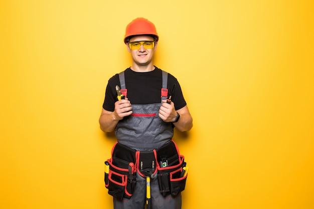 Het gelukkige knappe jonge werknemer glimlachen en duimen omhoog, kerel die workwear en riemmateriaal dragen
