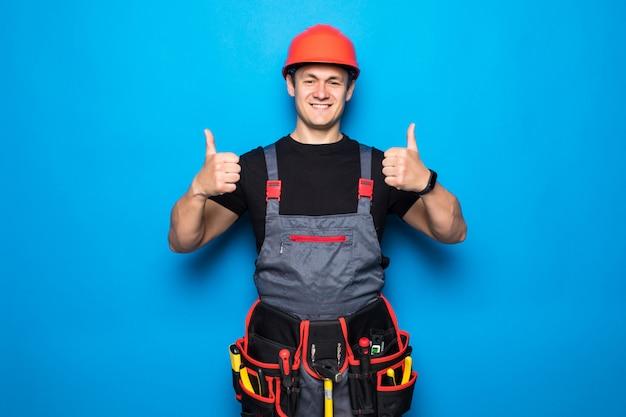Het gelukkige knappe jonge werknemer glimlachen en duimen omhoog, kerel die workwear en riemmateriaal en hemlet dragen