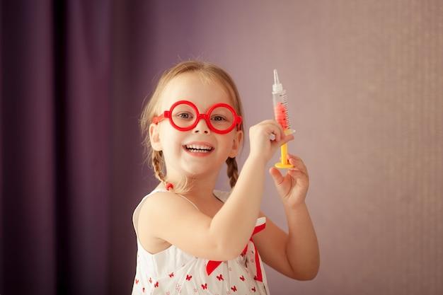Het gelukkige leuke blondemeisje met vlechten en het dragen van rode glazen speelt een arts