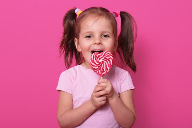 Het gelukkige leuke meisje draagt roze t-shirt, staat geïsoleerd op roze, houdt heldere lolly in handen. vrolijk kind met geopende mond die heerlijke snoepjes proeven. jeugd en smaken concept.