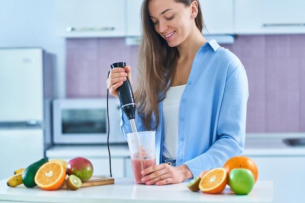 Het gelukkige leuke wijfje gebruikt handmixer om verse organische vruchten te mengen voor thuis dieet smoothie in de keuken voor te bereiden