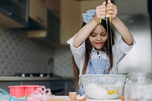 Het gelukkige meisje breekt eieren in de plaat