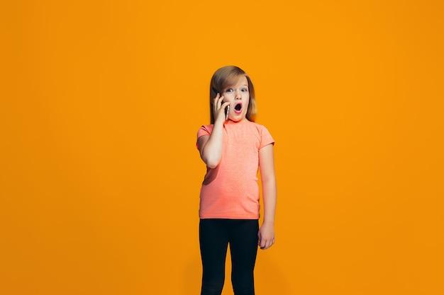 Het gelukkige meisje dat en zich tegen oranje muur bevindt glimlacht
