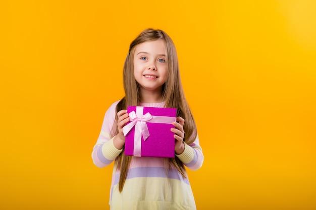 Het gelukkige meisje dat met lang haar een roze giftdoos op een gele ruimte houdt isoleert