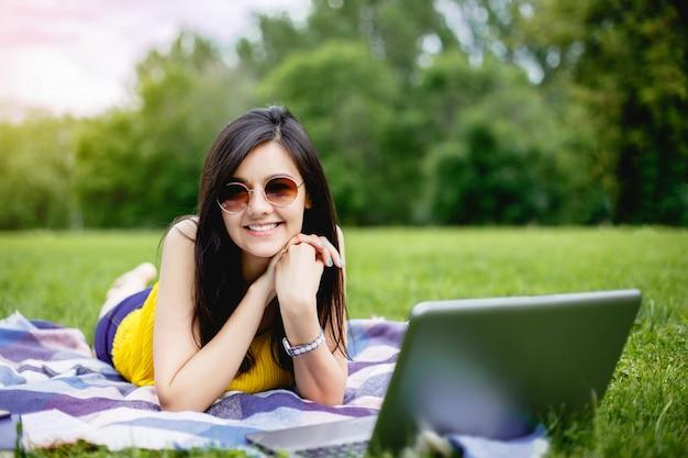 Het gelukkige meisje die van de tienerstudent laptop in een campus of een park gebruiken die op het gras liggen.