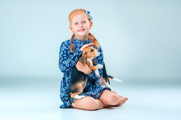 Het gelukkige meisje en een beagle puppie op grijze muur
