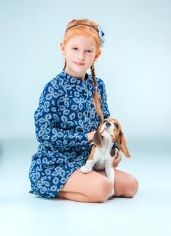 Het gelukkige meisje en een beagle puppy op grijze muur