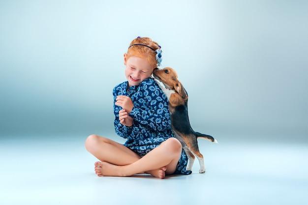 Het gelukkige meisje en een brakpuppy op grijze muur