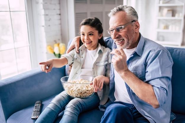 Het gelukkige meisje en een grootvader die televisie kijken met een popcorn