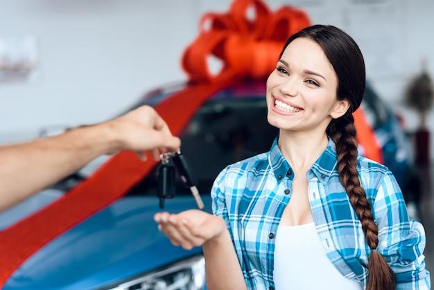 Het gelukkige meisje geeft de sleutels aan de nieuwe auto.