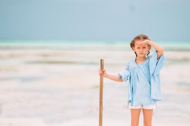 Het gelukkige meisje geniet de zomer van vakantie op het strand