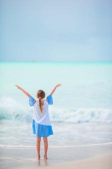 Het gelukkige meisje geniet van de achtergrond van de de zomervakantie de blauwe hemel en het turkooise water in het overzees
