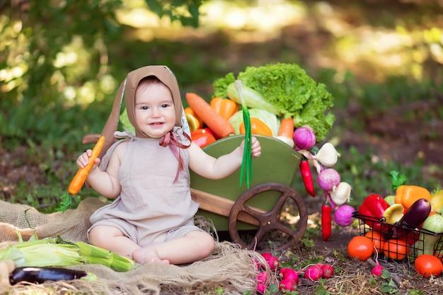 Het gelukkige meisje in een kostuum van een haas en een wortel in hand op aard verzamelt een oogst van groenten