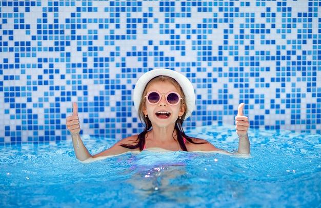Het gelukkige meisje in zonnebril en hoed met eenhoorn toont duim in openlucht zwembad van luxetoevlucht op de zomervakantie op tropisch strandeiland