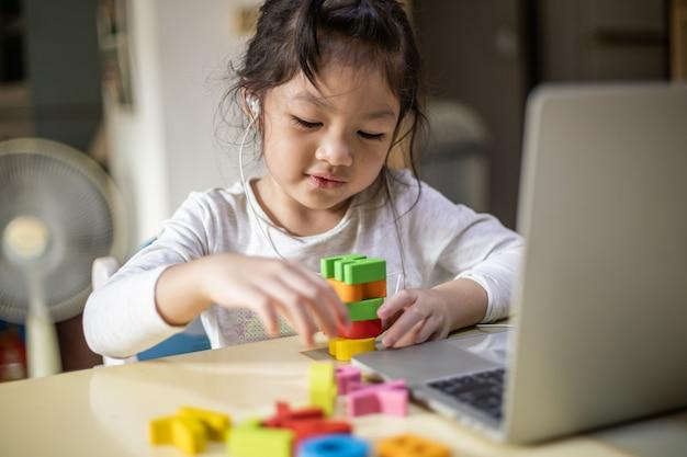 Het gelukkige meisje leert thuis online met laptop
