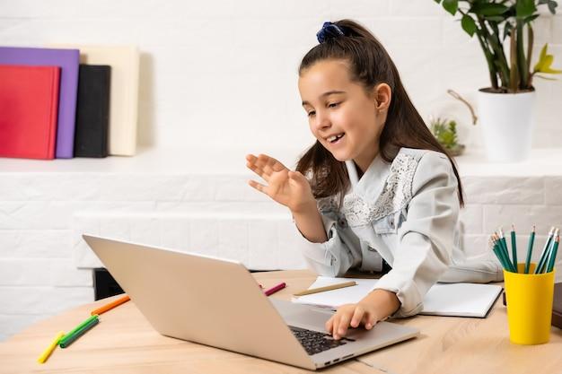 Het gelukkige meisje met een laptop aan de tafel