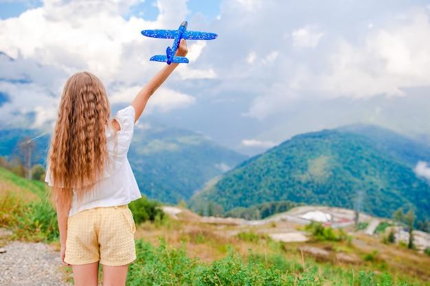 Het gelukkige meisje met stuk speelgoed vliegtuig dient binnen bergen in
