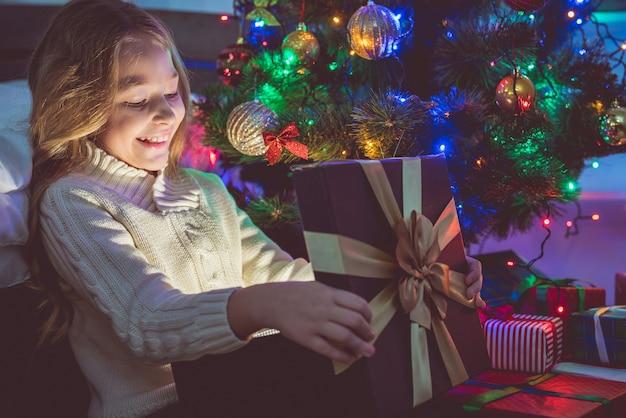 Het gelukkige meisje pakt een geschenkdoos uit op een kerstboomachtergrond. nachttijd
