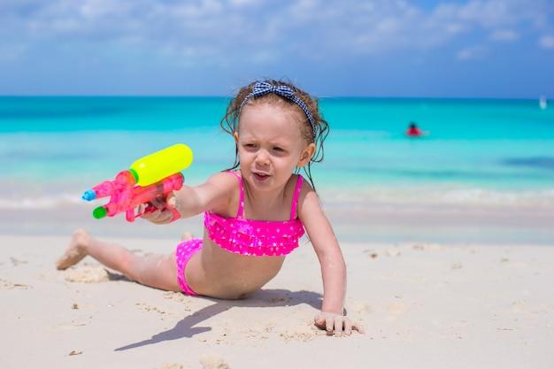 Het gelukkige meisje spelen bij strand tijdens caraïbische vakantie