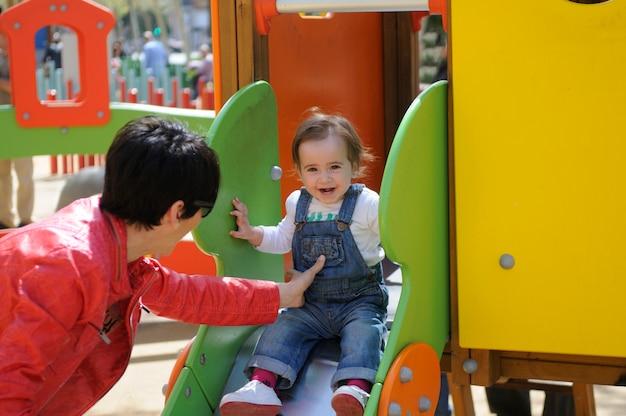 Het gelukkige meisje spelen in een stedelijke speelplaats.