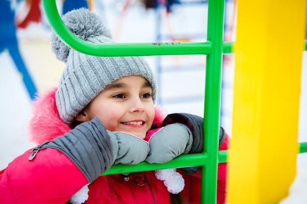 Het gelukkige meisje spelen op een speelplaats bij de winter ijzige dag.