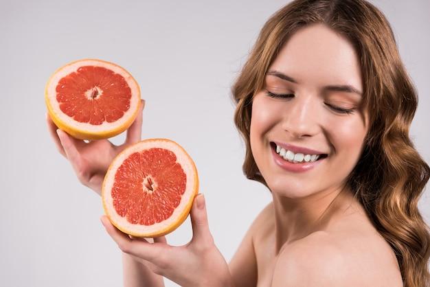 Het gelukkige meisje stellen met geïsoleerde grapefruit.