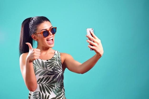 Het gelukkige meisje toont een signaal met haar duim omhoog terwijl het stellen in de studio en het nemen van een selfie op haar telefoon