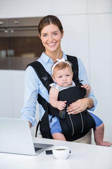 Het gelukkige meisje van de vrouwen dragende baby terwijl het gebruiken van laptop