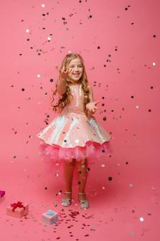 Het gelukkige meisje vangt confettien op roze ruimte, vakantieconcept