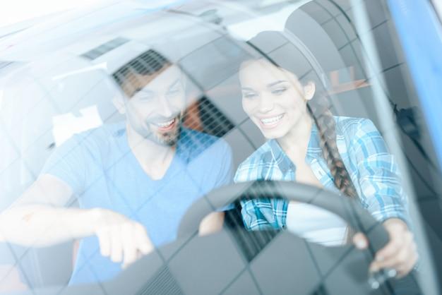 Het gelukkige meisje zit achter het stuur van een nieuwe auto en glimlacht.