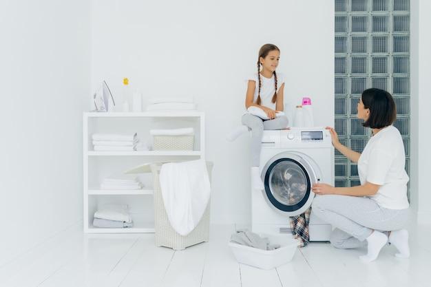 Het gelukkige meisje zit bij wasmachine, heeft prettig gesprek met moeder