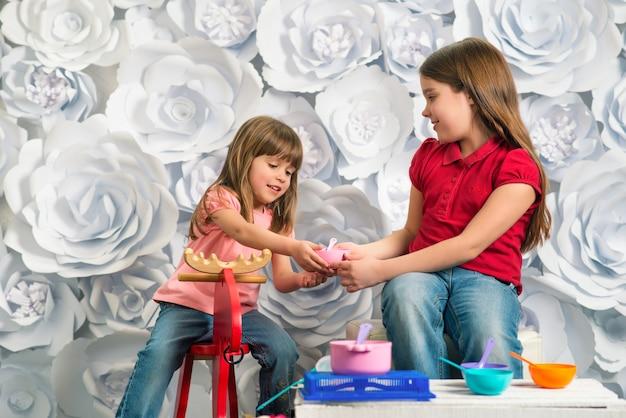 Het gelukkige meisje zit voor het speelgoed van kinderen