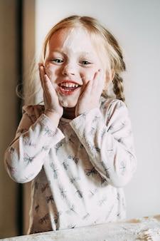 Het gelukkige meisjekind bevindt zich in het portret van het keukenclose-up en houdt haar eigen gezicht.