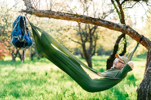 Het gelukkige mens ontspannen in hangmat het hangen op appelboom in de zomer zonnig park.